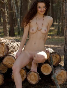Exciting brunette Karina shows her shaved pussy and puffy nipples in the forest