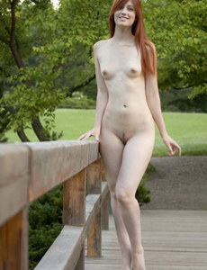 Young tall sexy beauty Nadi is nude outdoor on the wooden bridge