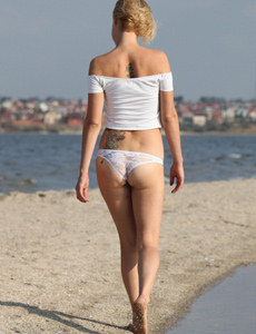 Beach blonde Larie with puffy nipples is wearing sexy white bikini before going nude