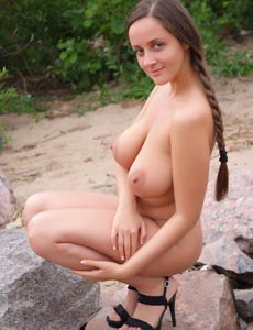 Eekat takes away her sexy white dress to show her nude big boobs posing on the rock at the shore