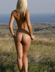 Exciting blonde Kittie with tiny tits and puffy nipples nude in the field near the forest