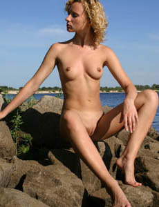 Leena shows her shaved pussy outside by the lake